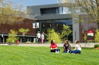 Student relaxing on the grass outside of the Science building